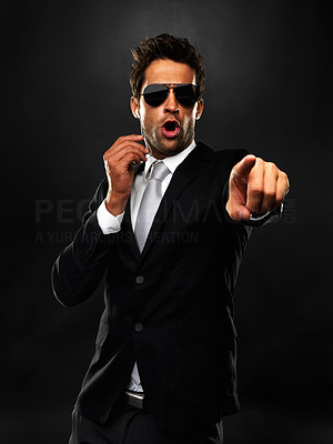 Buy stock photo Secret agent pointing at someone on black background
