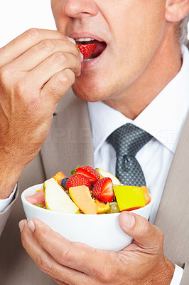 Buy stock photo Closeup shot of a businessman eating a fruit salad against a white background