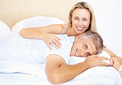 Buy stock photo Portrait of a cute romantic mature couple in bed together at home