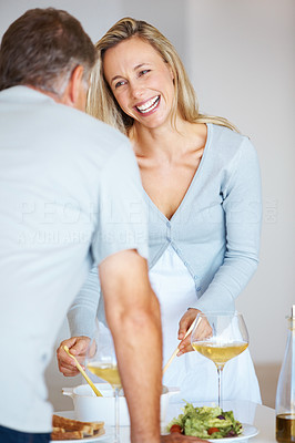 Buy stock photo Smiling pretty woman and her husband laughing while preparing food in their kitchen at home