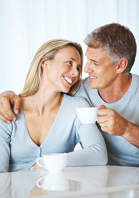 Buy stock photo Portrait of loving mature couple having cup of tea together indoors