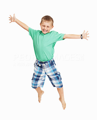 Buy stock photo Full length of cheerful young boy jumping in joy over white background