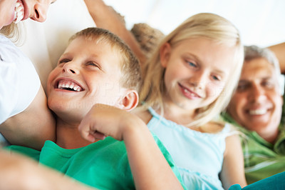 Buy stock photo Closeup of a happy young boy laughing with his mother on the couch, with his sister and dad in the background