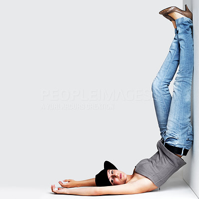 Buy stock photo Portrait of a cute young woman posing in upside down posture against grey background