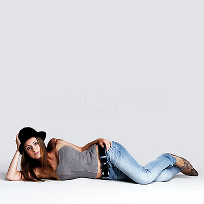 Buy stock photo Portrait of a beautiful young woman lying on the floor against grey background