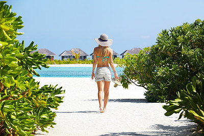 Buy stock photo Rear view of a sexy young woman walking along a path at a tropical beach