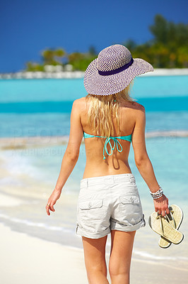 Buy stock photo Rear view of a beautiful young woman walking through the beach - Vacation