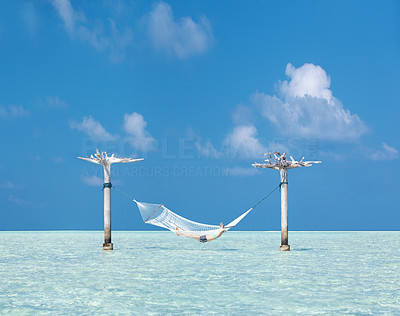 Buy stock photo Portrait of a young female resting on hammock build in between water - Sea