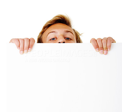 Buy stock photo Studio shot of a young man peering over a blank placard isolated on white