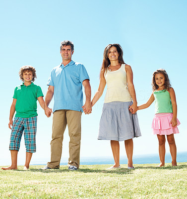 Buy stock photo Portrait of family holding hands and standing in row against clear blue sky