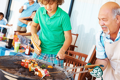 Buy stock photo Barbecuing - Senior man and grandson preparing steak with family in the background