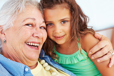 Buy stock photo Closeup portrait of grandmother embracing her cute little grand daughter