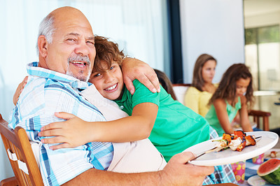 Buy stock photo Grandfather hugging his grandson during meal with family in background
