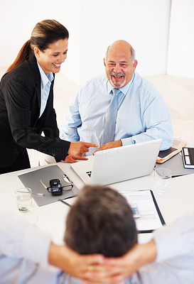 Buy stock photo Cheerful business executives looking at relaxed colleague in office