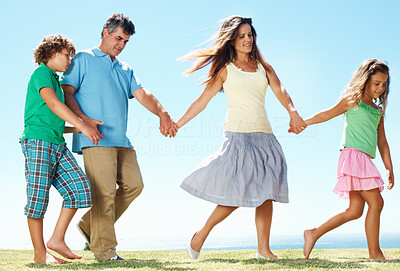 Buy stock photo Mature parents with their children walking together in park
