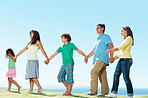 Family walking in row outdoors , holding hands
