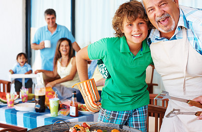 Buy stock photo Smiling grandad and grandson barbecuing together with happy family in background