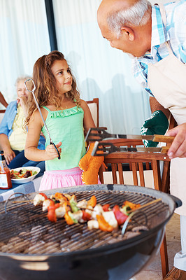 Buy stock photo Senior man and grand daughter barbecuing food with grandmother in the background