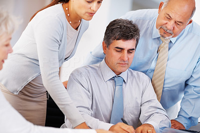 Buy stock photo Mature business man signing contract during a meeting