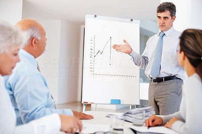 Buy stock photo Mature businessman making presentation to his colleagues at the office