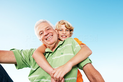 Happy young boy giving hug from back to his grandfather