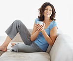 Beautiful smiling woman holding a coffee cup on couch