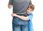 Smiling little boy hugging his father against white