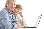 Happy senior couple browsing together on laptop