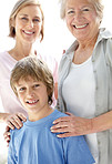 Adorable small boy standing with his mother and grandmother