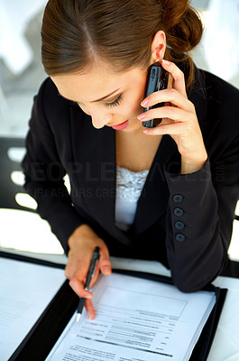 Buy stock photo Shot of a young businesswoman talking on her cellphone while looking through paperwork
