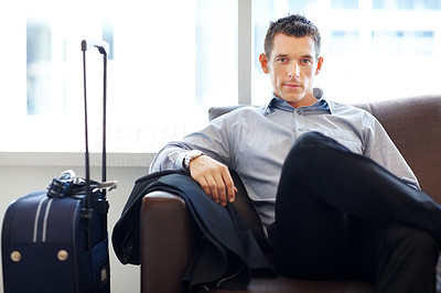 Young business executive waiting for his flight at airport