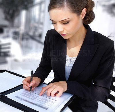 Buy stock photo Shot of a young businesswoman sitting at a table looking over paperwork