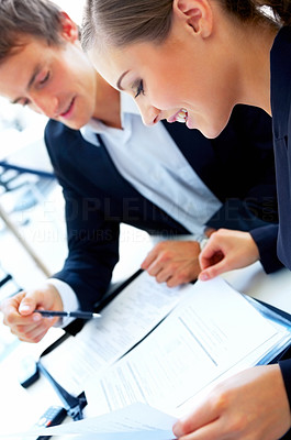 Buy stock photo Shot of a two businesspeople sitting a table talking together over paperworkdf