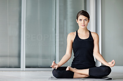 Cute young female practicing yoga on a mat in the lotus pose