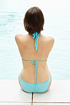 Rear view of a stunning female sitting at the pool