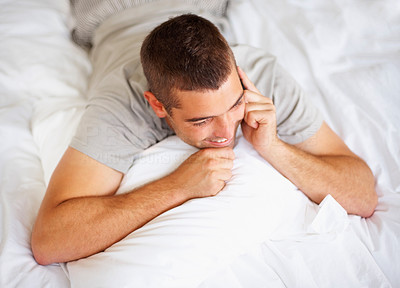 Happy young guy talking on mobile while lying on bed