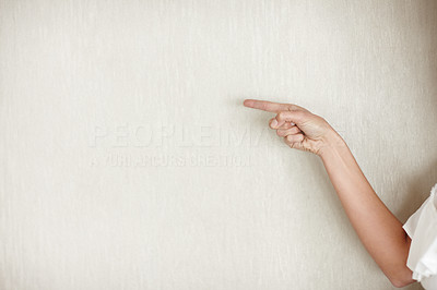 Human hand pointing towards a wall