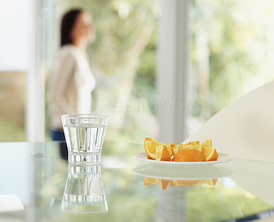 Sliced oranges and glass of water with a person at the back
