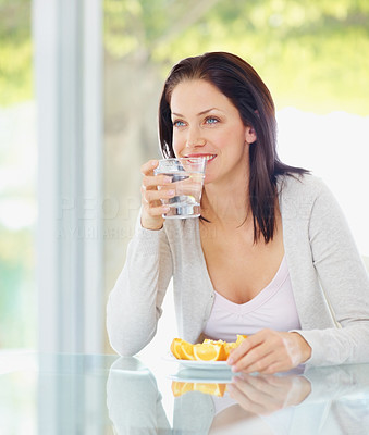 Beautiful female drinking a glass of water and eating oranges