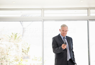 Happy elderly business man reading text message at office