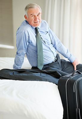 Happy mature man sitting on bed with his luggage
