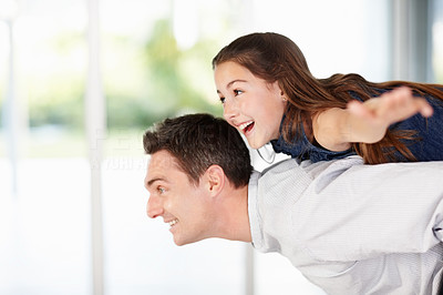 Happy middle aged man giving young girl piggyback ride