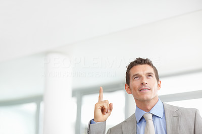 Middle aged business man pointing up - copyspace