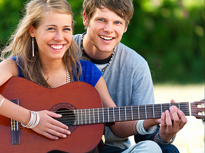 Young couple playing the guitar together