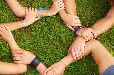 Closeup of young friends holding hands on grass
