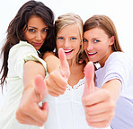 Closeup portrait of happy young friends standing together and showing thumbs up sign