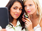 Closeup of two happy beautiful young women looking into a mirror