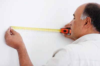 Man taking measurements of a wall with measuring tape