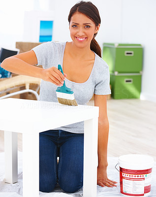 Portrait of a happy teenage girl painting white color to a table
