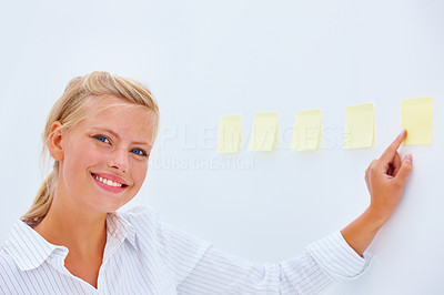 Smiling businesswoman pointing at adhesive notes on wall